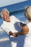 A terra arrendada sênior feliz da dança dos pares entrega a praia Imagens de Stock
