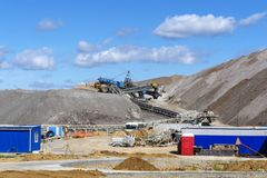 Terra-cone with belt conveyor system. Dumps of mined rock with belt conveyors, stackers and working bulldozer, general view royalty free stock photo