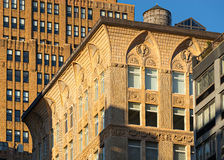 Terra Cotta Ornament of Chelsea loft building, New York City. Sunlit architectural detail of upper floors of a loft building in Chelsea, Manhattan, New York City stock image