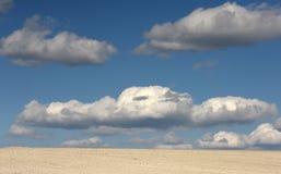 Terra da argila e nuvens brancas no céu azul Foto de Stock
