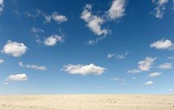 Terra da argila e nuvens brancas no céu azul Fotos de Stock
