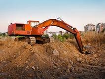 Terra de escavação da máquina perto da cidade Fotografia de Stock