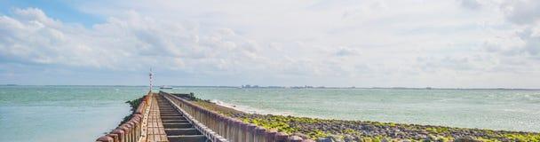 Terra de proteção do dique contra o mar na luz solar Fotografia de Stock