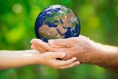 Terra della tenuta dell'uomo e del bambino in mani Immagini Stock Libere da Diritti