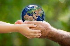 Terra della tenuta dell'uomo e del bambino in mani Immagini Stock