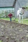 Terra di lavoro del ragazzo adolescente dell'agricoltore nel modo tradizionale con il cavallo e l'aratro Fotografia Stock Libera da Diritti