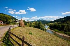 Terra di un agricoltore vicino al fiume della montagna con una scossa di fieno Fotografie Stock Libere da Diritti