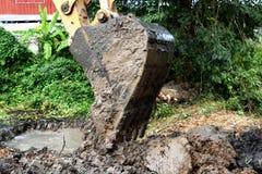 Terra di vangata dell'escavatore a cucchiaia rovescia fotografia stock libera da diritti