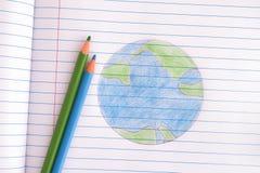 Terra do planeta tirada com os lápis na folha do caderno Fotografia de Stock