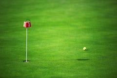 Terra e palla verdi di golf vicino al foro Fotografie Stock