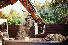 Terra movente da máquina escavadora do Backhoe no canteiro de obras fotografia de stock