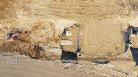 Terra muoventesi e scarico dell'escavatore del caricatore del camion industriale video d archivio