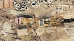 Terra muoventesi e scarico dell'escavatore del caricatore del camion industriale stock footage
