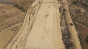 Terra muoventesi e scarico dell'escavatore del caricatore del camion industriale archivi video