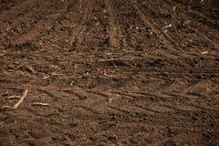 Terra non lavorata, campo con le careggiate in primavera Struttura della sporcizia Struttura del giacimento della sporcizia del p fotografia stock libera da diritti