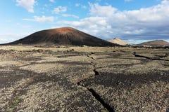 Terra rachada no parque nacional de Timanfaya, montanhas no fundo Lanzarote fotos de stock royalty free
