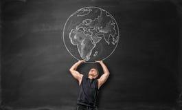 A terra representada no quadro-negro e no homem desportivo que actuam como o está guardando acima acima dsi mesmo Imagens de Stock