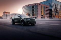 Terra Rover Range Rover Evoque dell'automobile che sta sulla strada asfaltata in città Mosca al tramonto Fotografia Stock Libera da Diritti