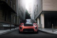 Terra Rover Range Rover Evoque dell'automobile che sta sulla strada asfaltata in città Mosca al tramonto Immagini Stock Libere da Diritti