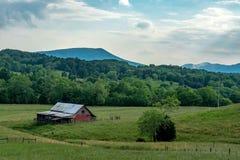 Terra scenica dell'azienda agricola di rotolamento con il vecchio granaio rosso Fotografia Stock