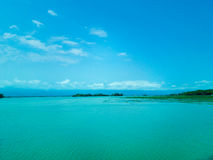 Terra sotto acqua con cielo blu Fotografia Stock
