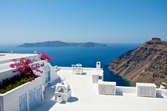 On the terrace. With snow-white terraces with amazing views. In the distant mountains are visible islands, the blue Mediterranean Sea stretches to the horizon Stock Photos