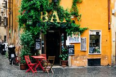 Terrace of a bar or cafe in the Trastevere of Rome, with red chairs and table. Warm tones and moisture shines on the floor. stock photos