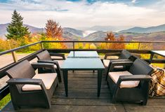 Terrace with beautiful view in to the mountains. Autumn season with red foliage on forested hills. cloud inversion in distant valley. wonderful vacation royalty free stock image