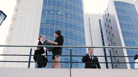 The terrace of business center and business people doing their business. The terrace of big business center and business people: two women and a man doing their stock video footage