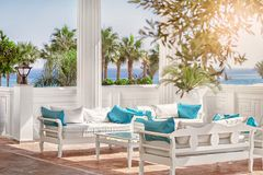 Terrace with columns, white benches with blue pillows by the sea and the palm alleys in a sunny day. Terrace with columns, glass table and white benches with Royalty Free Stock Photos