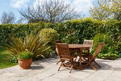 Terrace and garden furniture. Terrace in pavement and wooden garden furniture in a garden royalty free stock photos