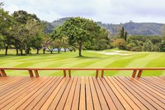 Hardwood decking or flooring and view of green field in golf course. Garden decorative. Terrace of hardwood decking or flooring and view of green field in golf royalty free stock images