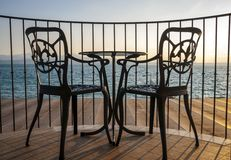 Terrace lake view with iron chairs and table Royalty Free Stock Photos