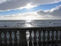 Terrace overlooking the sea with concrete balustrade . There are giants cumulonimbus clouds in the sky with sun rays through Royalty Free Stock Photos