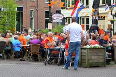 People have fun at a cosy terrace with Dutch flags, Kingsday (Koningsdag) in Baarn, Netherlands  Royalty Free Stock Photos