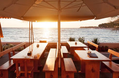 Terrace restaurant tables under parasol at sunset Stock Photo