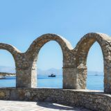 Terrace with stone arch.  Scenic  view of the sea, mountains and. Ships. Greece. Concept - travel, tourism, vacation Royalty Free Stock Image