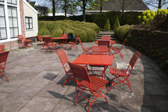 Terrace in a sunny garden. Colorful terrace in a sunny garden with red tables and chairs and in the back boxwood hedges Stock Photos