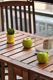 Terrace table and decoration. Terrace table decorated with two ceramic apples and a plant Royalty Free Stock Images