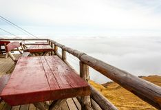 Terrace with tables and wooden benches on mountain summit. Cloud. S cover and cable seen in the background stock photo