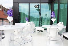 Terrace with transparent chair. Shot of terrace in winter with infra red heating device and transparent chairs and white tables Stock Photo