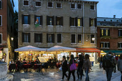 Terrace of a typical pizzeria restaurant in Piazza San Geremia with people eating and walking Royalty Free Stock Images