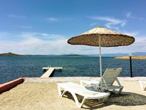 Terrace with a view on sea. Umbrellas and lounge chair in a sunlight. Royalty Free Stock Photos