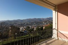 Terrace of vintage villa. Nobody inside. Balcony of a period villa with a fantastic view of the city of Lugano with the mountains behind. Wonderful day Stock Images