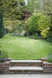 Terraced garden with lawn and patio royalty free stock photos
