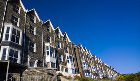 Terraced Housing in Wales UK. Wide view of a long row of greystone terraced houses against a blue sky. Barmouth, Wales, UK stock photography