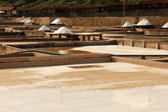 Terraces salt mine. Parcial view of a salt mine located in Rio Maior - Portugal.  the terraces and pine boards with plenty of white salt and a old village from Royalty Free Stock Images