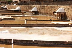 Terraces salt. Parcial view of a salt mine located in Rio Maior - Portugal.  the terraces and pine boards with plenty of white salt and a old village from salt Royalty Free Stock Image