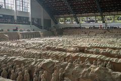 Terracotta Army warriors buried in Emperor tomb outside Xian China. XI`AN, CHINA - 17 OCTOBER 2018: Tourists inside building housing the pottery terracotta army royalty free stock image