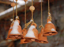 Terracotta Bells. Part of a wind chime, hanging up in a garden in the snow Royalty Free Stock Photo